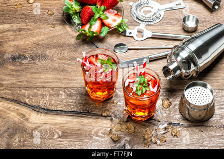Red drink with ice. Cocktail making bar tools and shaker - Stock Photo