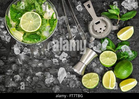 Cold drink glass with lime, mint leaves, ice. Mojito, caipirinha, lemonade, tonic water - Stock Photo