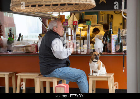 Man and dog sitting at bar on the beach in Barcelona, Spain. W Hotel in the distant background. Black and white - Stock Photo