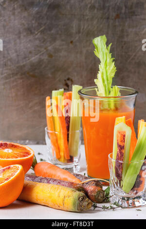 Sliced colorful raw carrots and celery as vegetarian snack, blood oranges and thyme with glass cup of fresh orange - Stock Photo