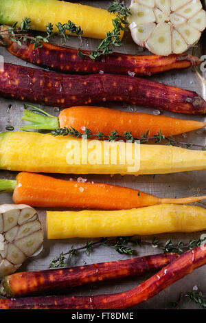 Close up of Ready for baking peeled colorful raw carrots with oil, fresh thyme herbs and sliced garlic in aluminum tray. Top vie