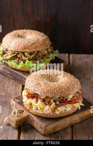 Two Bagels with stew beef, fresh salad, bacon, scrambled eggs and fried onion served on small wooden chopping boards - Stock Photo