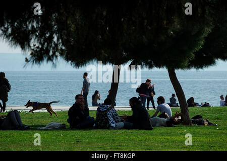 People enjoy a sunny day by having a picnic at the seafront park next to the White Tower monument of Thessalonica - Stock Photo