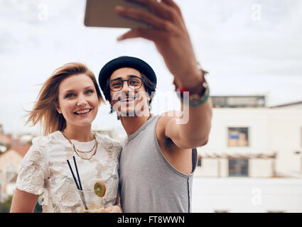 Two young friends taking self portrait with smart phone during a party. Young man and woman taking selfie at rooftop - Stock Photo