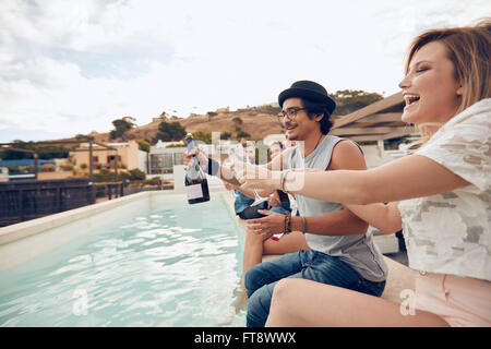 Outdoor shot of happy young people sitting on the edge of the pool drinking champagne. Multiracial friends enjoying - Stock Photo