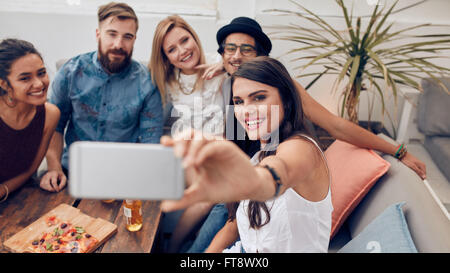 Multiracial people enjoying in party taking a self portrait with mobile phone. Group of young friends sitting on - Stock Photo