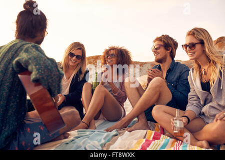 Group of young people listening to friend playing guitar outdoors. Diverse group of friends hanging out at beach. - Stock Photo