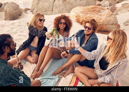 Group of young people toasting beers while sitting at the beach. Mixed race friends celebrating with drinks at beach - Stock Photo