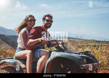 Portrait of loving young couple cruising over country roads by quad vehicle. Happy man and woman driving a quad - Stock Photo