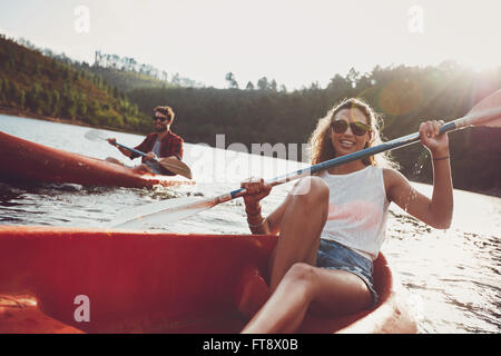 Beautiful young woman kayaking in a lake with man paddling in the background. Young couple canoeing on summer day.