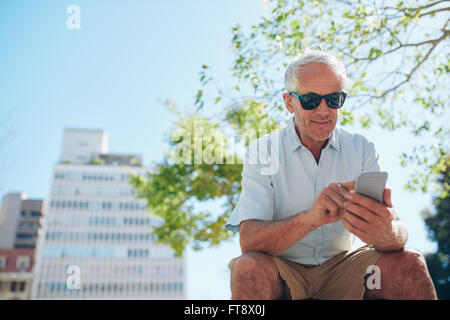 Low angle view of mature man sitting outdoors using mobile phone. Mature tourist resting outside in the city and - Stock Photo
