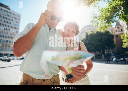 Senior couple looking at city map. Mature man and woman outdoors in city reading a map for direction.