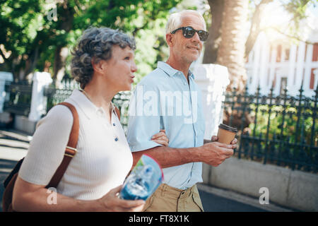 Senior man and woman walking in the city. Mature tourist roaming in a town during their vacation. - Stock Photo