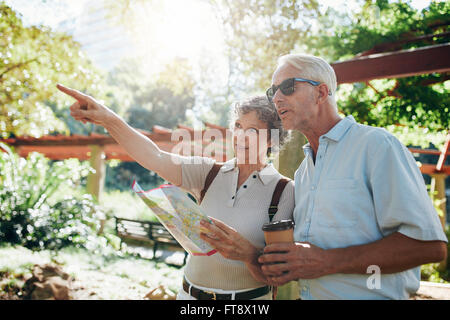Couple of senior tourists using a city guide searching locations and pointing - Stock Photo