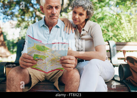 Senior tourist sitting on a park bench reading city map. Man and woman using city guide for finding their location. - Stock Photo