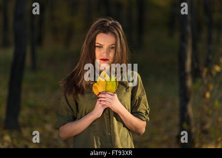 Pensive autumn look. A meditative teenage girl is looking down in a autumn forest while holding yellow leaves in - Stock Photo