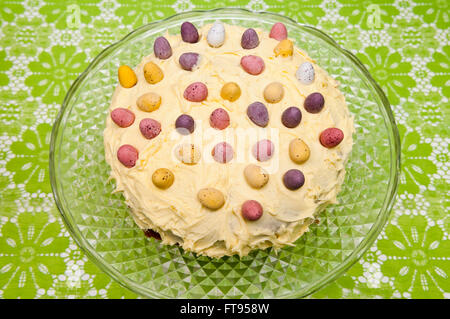 A homemade round Easter cake decorated with lemon butter cream and chocolate mini eggs on a vintage glass cake stand - Stock Photo