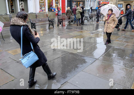 Bath, UK. 26th March, 2016. Tourists photographing themselves outside of Bath Abbey are pictured as they brave heavy - Stock Photo