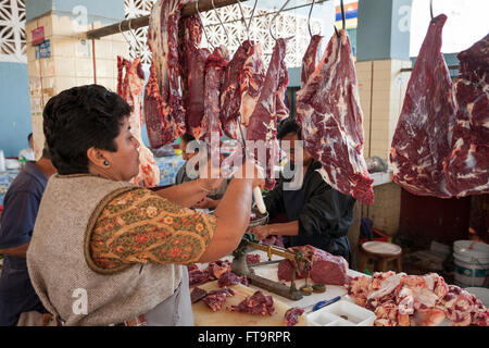 Making stewing beef in the market. A woman butcher slices a strip of beef from a large hanging piece of beef. - Stock Photo