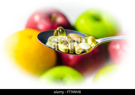 Assorted Vitamins and Nutritional supplements in serving spoon. on blur colorful fruits background - Stock Photo