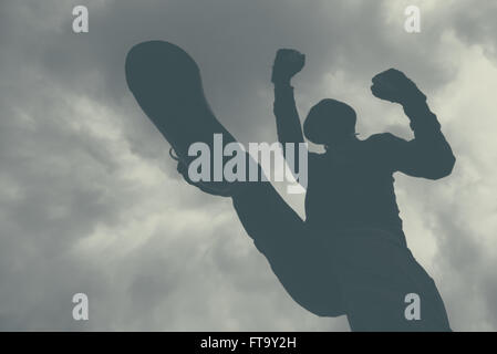 Violent attack, unrecognizable hooded male criminal kicking and punching victim on the street. monochromatic image. - Stock Photo