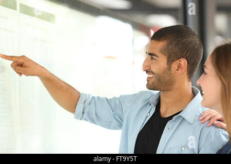 Arab man and his girl friend consulting schedule in a bus or train station pointing with his hand - Stock Photo