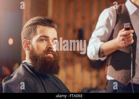 Bearded man sitting in the barbershop - Stock Photo