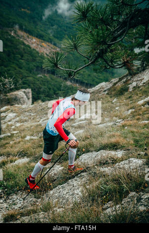 male athlete climbs on foot uphill during Mountain marathon - Stock Photo
