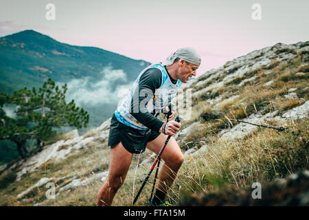 middle-aged man with walking sticks is on side of mountain during Mountain marathon - Stock Photo