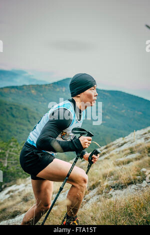 young athlete with nordic walking poles is on side of mountainduring Mountain marathon - Stock Photo