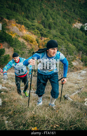 young athlete marathon runner is ahead of his opponent on a mountain trail - Stock Photo