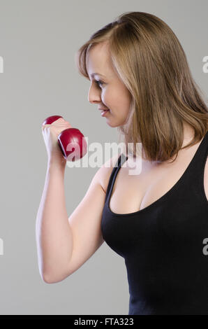 Beautiful young woman working out with dumbbells - Stock Photo