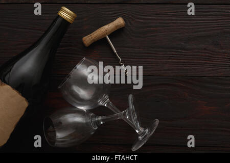 Bottle of red wine with blank label next to to two empty glasses with corkscrew on wooden table. Flat lay, above - Stock Photo
