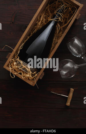 Bottle of red wine in wooden crate filled with straw next to to empty glasses with corkscrew on wooden table. Flat - Stock Photo