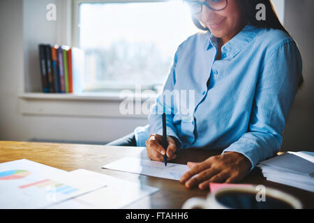 Selective focus close up of cheerful young self-employed woman wearing glasses and blue shirt at desk writing on - Stock Photo