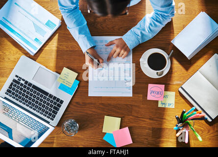 Businesswoman working on a report or questionnaire writing notes with a pen, overhead view of her desk with a laptop, - Stock Photo
