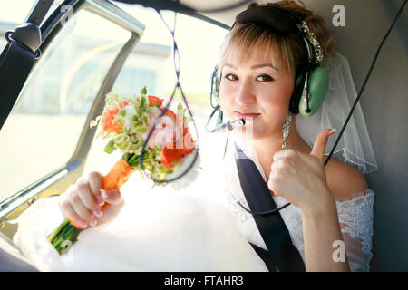 Bride inside helicopter preparing to fly, in headset, thumbs up. - Stock Photo