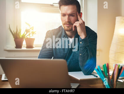Frowning businessman reading information on his laptop with a serious engrossed expression as he ponders the solution - Stock Photo