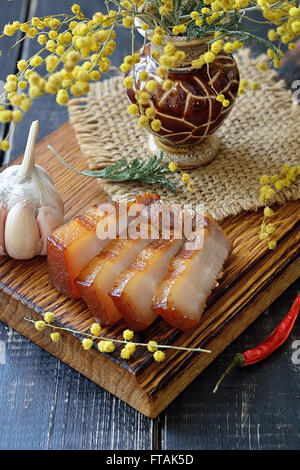Slices of bacon on a wooden board - Stock Photo