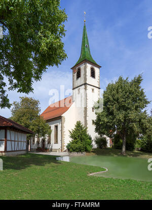 Old rural church on a small pond in a village - Stock Photo