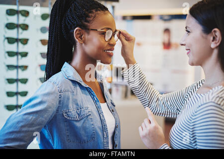 Optometrist helping a pretty African client to try on and purchase frames for a pair of eyeglasses - Stock Photo