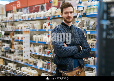 Confident handyman in a hardware store standing amongst the racks of products with folded arms smiling at the camera - Stock Photo