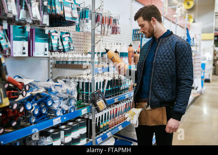 Young handyman or DIY homeowner in a store standing selecting a product in the hardware department and reading the - Stock Photo