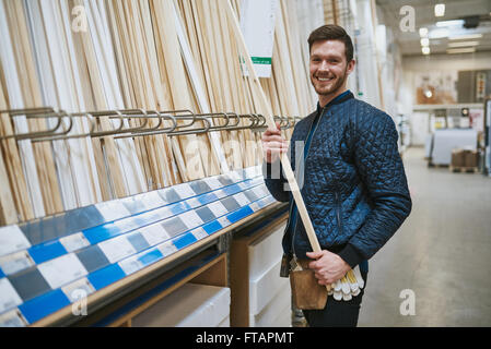 Happy confident young carpenter or handyman standing in a hardware store purchasing lengths of cut timber from the - Stock Photo