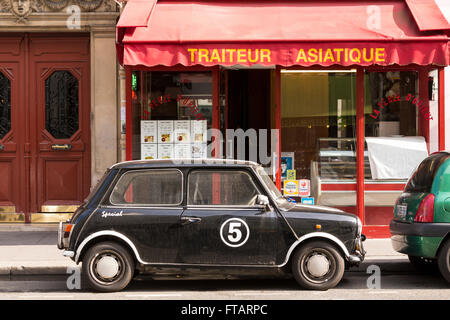 Typical Paris street scenes: a small, retro-styled car parked in front of a Chinese restaurant - Stock Photo