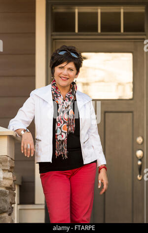 Happy, confident, mature, middle-aged woman standing in front of a house. She could be the home owner or a real - Stock Photo
