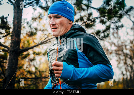 Beloretsk, Russia -  September 26, 2015: closeup of male runner of middle-aged runs through forest during marathon - Stock Photo