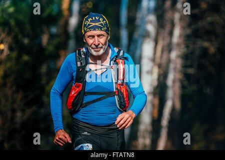 Beloretsk, Russia -  September 26, 2015: beautiful smiling senior man years running through woods during marathon - Stock Photo