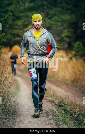 Beloretsk, Russia -  September 26, 2015: young male runner running through forest road during marathon mountain - Stock Photo