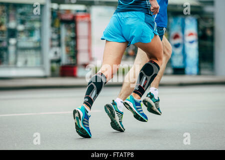 Omsk, Russia -  September 20, 2015: two athletes running through streets of city during Siberian international marathon - Stock Photo